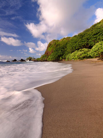 portrait orientation of Hamoa Beach on the island of Maui with a blue and a wave across the sand in the foreground