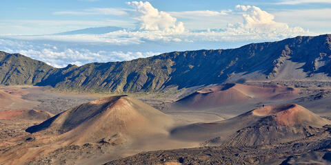 looking across Haleakala crater on the island of Maui with cinder cones in the foreground.  Mauna Loa and Mauna Kea can be seen in the distance miles away