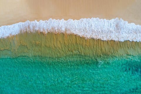 Big beach shorebreak aerial view with golden sand and beautiful Maui water.  Photographed by Andrew Shoemaker