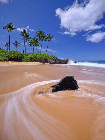 a clear blue sky image at Chang's beach in Makena on the island of Maui with water motion around the rocks