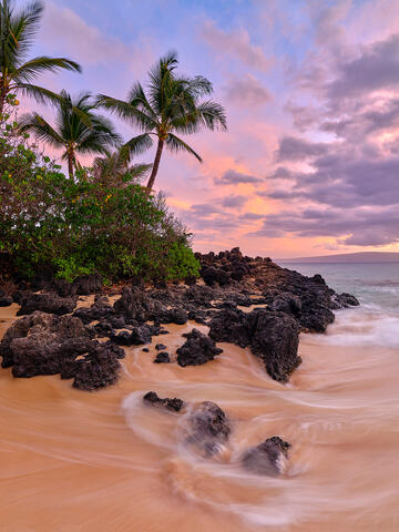 A beautiful vertical photo with silky water, coconut palm trees and a colorful pastel sunset at Secret Beach in Makena.  Photographed by Andrew Shoemaker