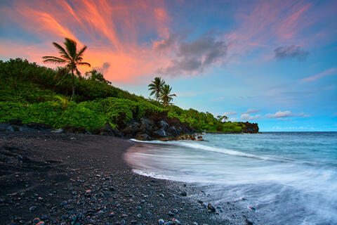 A glorious sunset at the black sand beach of Waianapanapa State Park in Hana, Hawaii.   Incoming wave crashes on to the beach