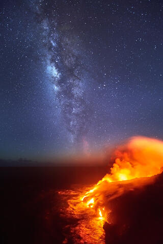 the volcanic lava meets the pacific ocean at Hawaii Volcanoes National Park with the stars and Milky Way galaxy rising over the pacific.