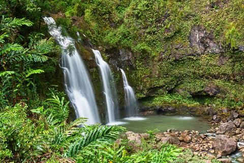 upper Waikani Falls or Three Bears flows into the lush canyon on the road to Hana on the island of Maui