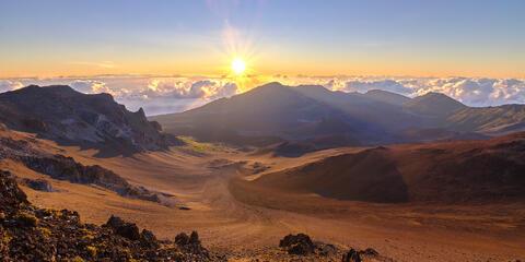 sunrise panorama overlooking Haleakala Crater with a sunstar at Haleakala National Park on the island of Maui