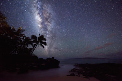 The core of the milky way galaxy rises over Secret Beach (also known as Makena Cove) at night on the island of Maui, Hawaii