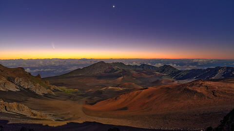 panoramic view of Haleakala Crater just before sunrise with the Neowise comet on the horizon
