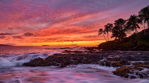stunningly vibrant sunset at secret beach in Makena on the island of Maui with incoming waves over the lava rocks.  Photographed by Andrew Shoemaker