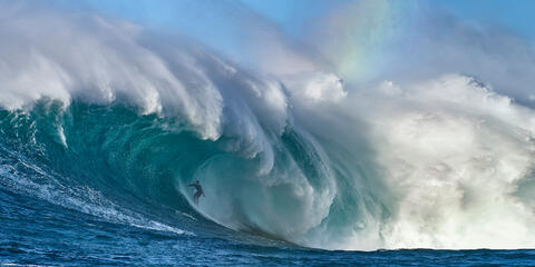 the biggest wave in Hawaii Jaws also known at Peahi with surfer Kai Lenny in the barrel and a rainbow visible from the spray.  Photographed by Andrew Shoemaker
