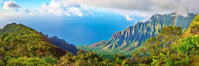 a panorama of the Kalalau valley along the Na Pali coast on the Hawaiian island of Kauai featuring a rainbow and dramatic light.  Fine Art Hawaii Photography