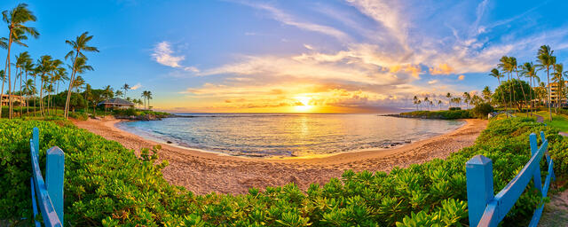 panoramic capture of the beautiful Kapalua Bay Beach Maui at sunset with a blue fence and surrounded by palm trees.  Fine art by photographer Andrew Shoemaker