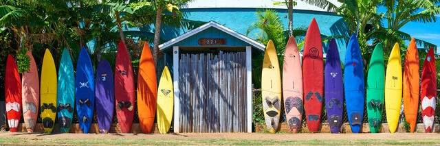 a very colorful surfboard fence in the same sequence as the rainbow found in Paia on the north shore of Maui