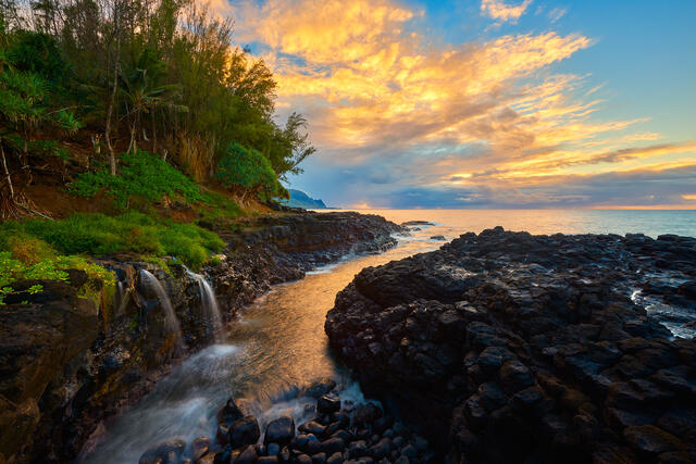 sunset at Queen's Bath on the island of Kauai with a waterfall flowing into the ocean along the lava rock.  Fine art photography by Andrew Shoemaker