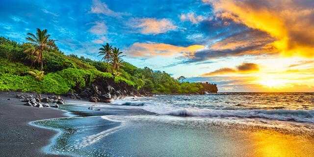 a vibrant sunrise at the famous black sand beach at Waianapanapa State Park near Hana on the island of Maui, Hawaii.