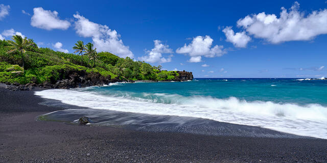 panoramic daytime view of the black sand beach at Waianapanapa State Park near Hana on the island of Maui with an incoming wave