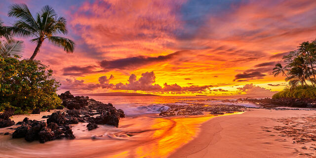 a panoramic view of a vibrant orange, red, and blue sunset at Secret Beach in Makena Maui