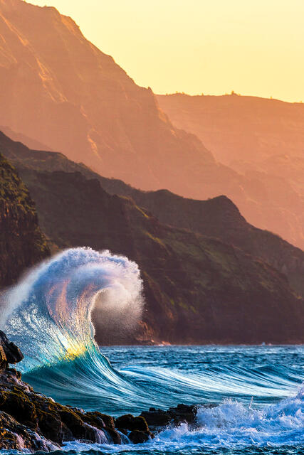 waves collide with each other at sunset along the Na Pali coast of Kauai.  The sunset colors are present in the wave itself