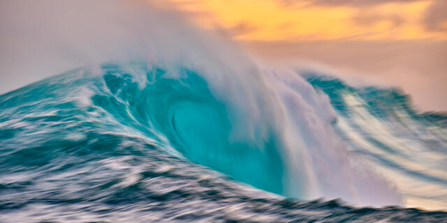 a slow motion capture of the biggest wave in Hawaii Jaws with a vibrant colorful sunrise