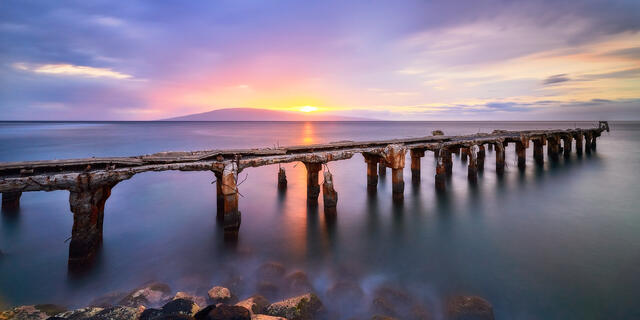 long exposure sunset panoramic photograph at Mala Ramp in Lahaina, Maui.   The sun is setting behind the island of Lanai and creating a purple tone throughout t