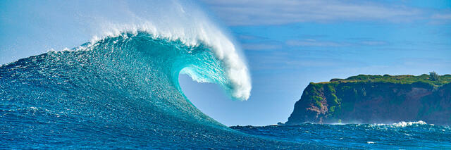 a very special moment at Jaws was captured here with the wave breaking and Maui's sea cliffs in the background.  The wave is illuminated by the sun and one of m