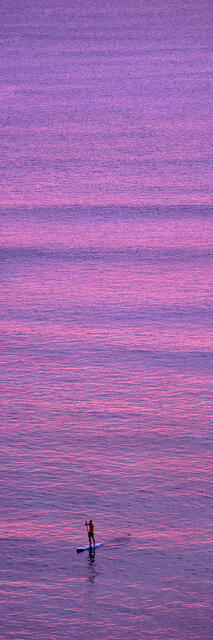 a stand up paddle surfer at sunset paddles towards the shore at Waikiki beach on the island of Oahu, Hawaii.  Vertical panorama photography by Andrew Shoemaker