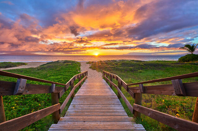 looking down a staircase to the beach at Kamaole 2 in Kihei Maui with a colorful sunset over the ocean in the background.
