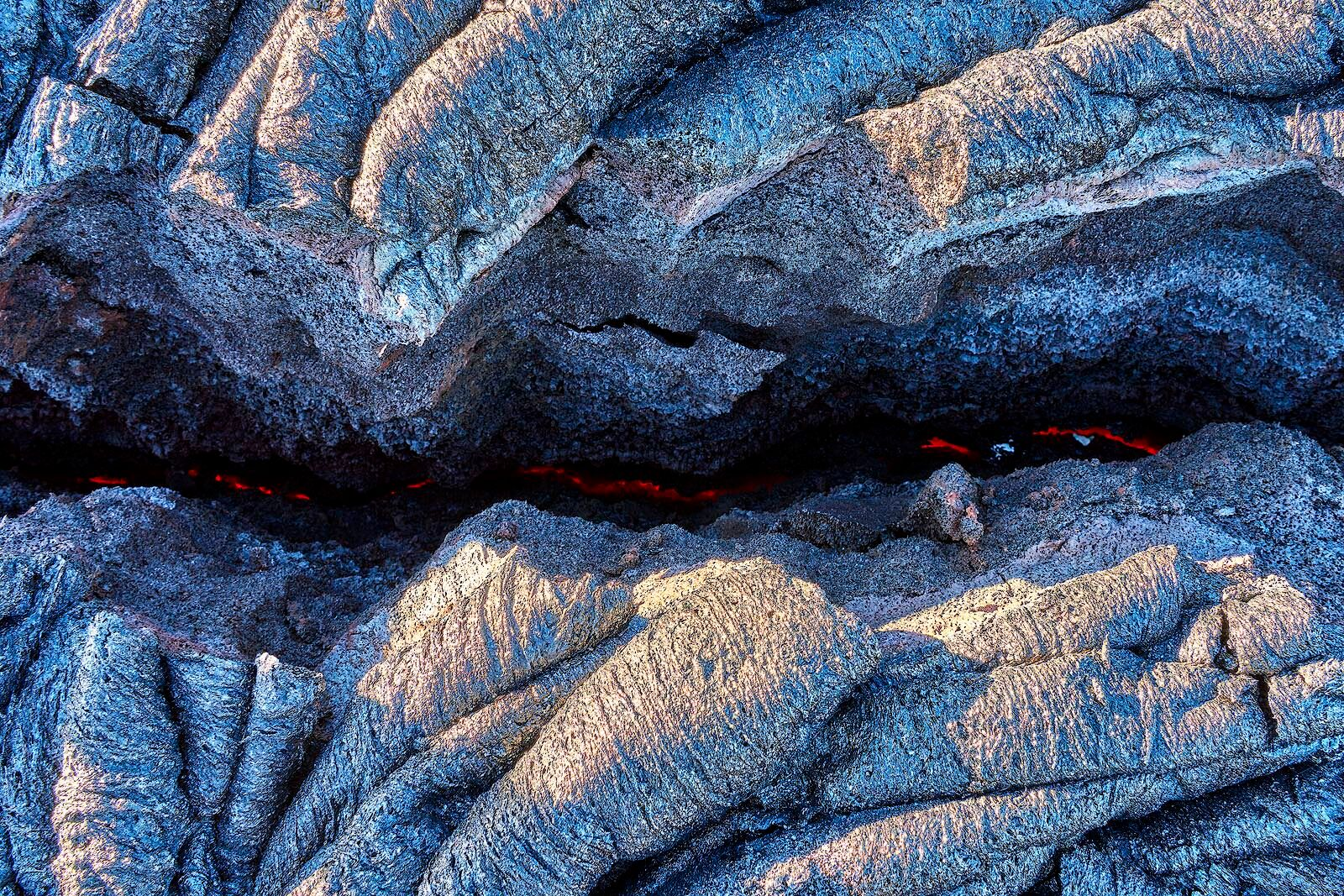 the earth is glowing red hot through a crack in the dried lava on the big island of Hawaii.  Lava Photography by Andrew Shoemaker
