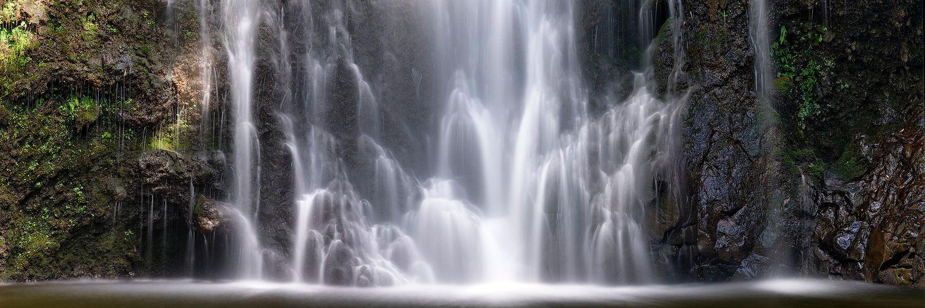 panorama at the base of Wailua Falls near Hana on the island of Maui with beautiful misty water due to a longer exposure