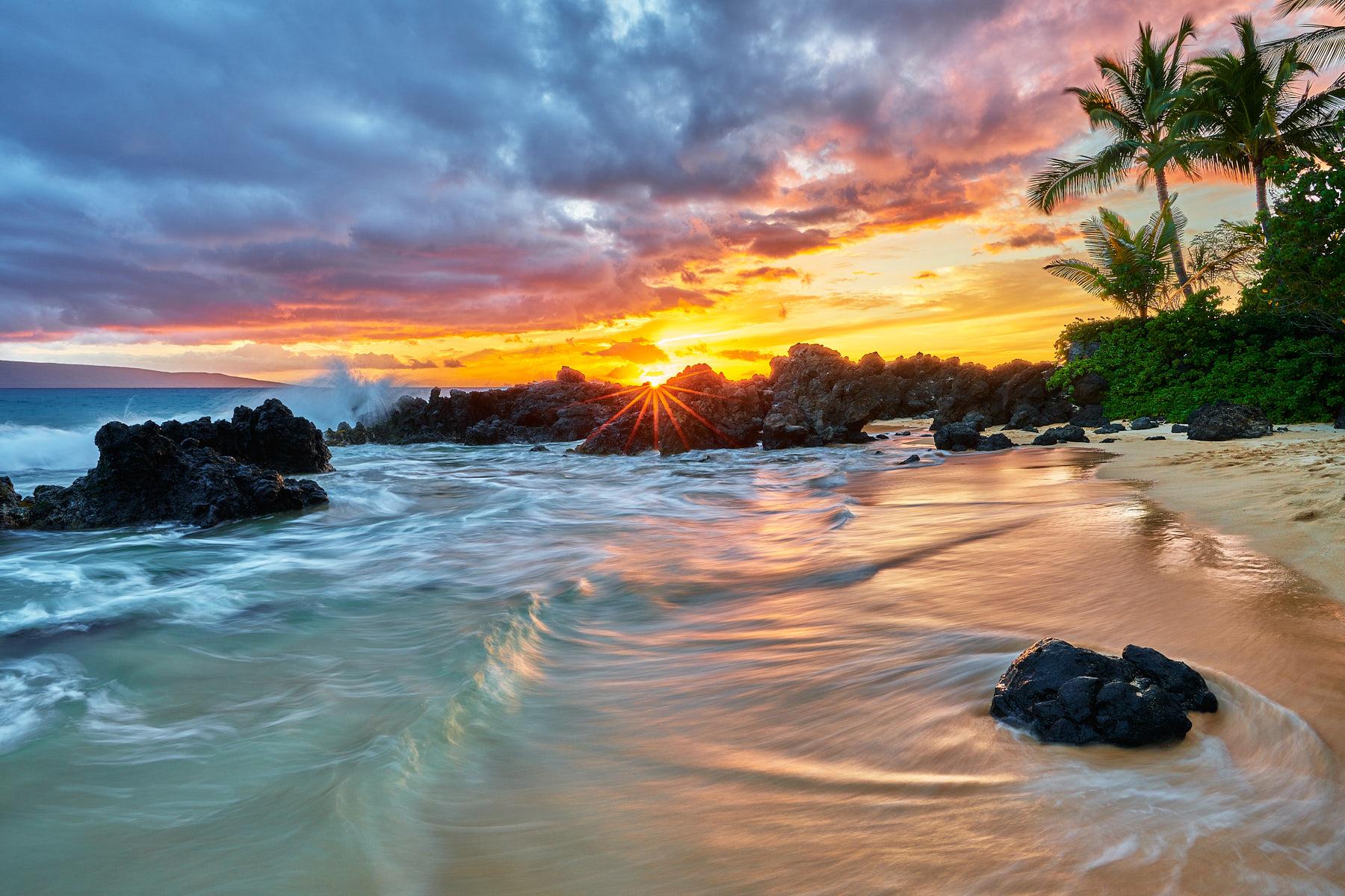 beach sunset on a golden sand beach just south of Secret Beach in Makena on the island of Maui with a sun star