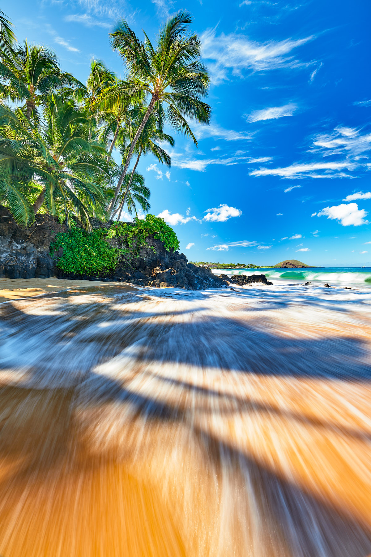incoming waves at a small secret cove make a beautiful morning scene with coconut palms sticking out from the land in Makena, Maui