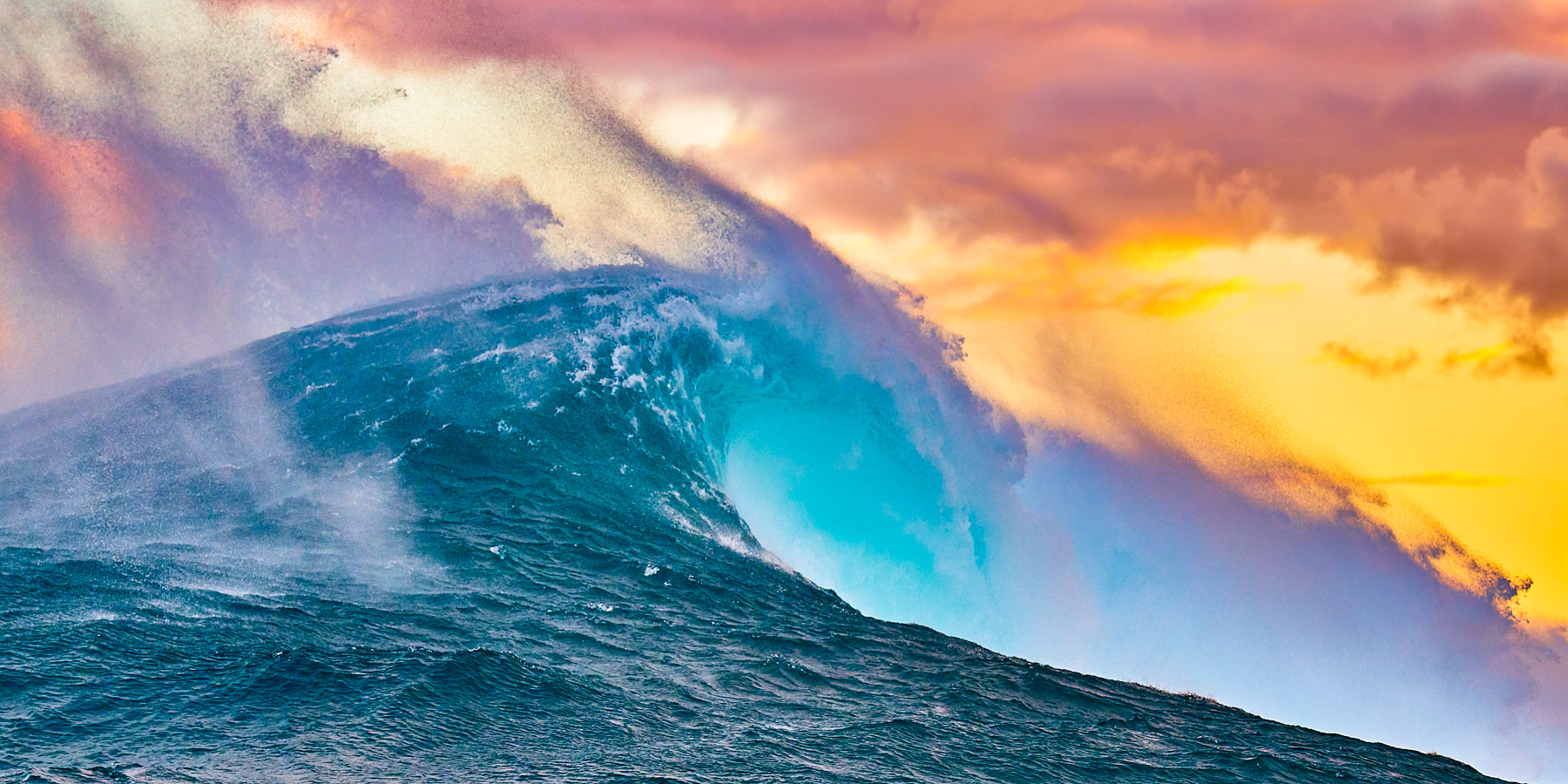 panoramic photograph of the biggest wave in Hawaii Jaws at sunrise with very vibrant and dramatic colors.  Photographed on the North Shore of Maui