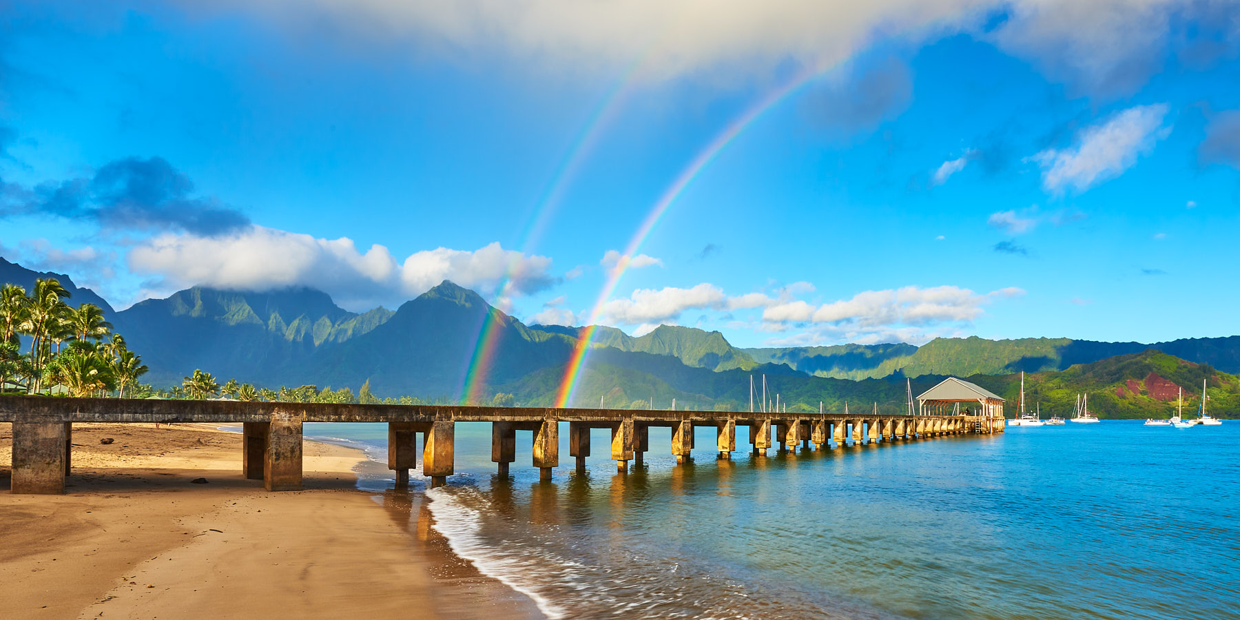 the beautiful Hanalei Bay Pier in the morning with a double rainbow over the pier and the lush towering mountains of Hanalei Kauai in the background