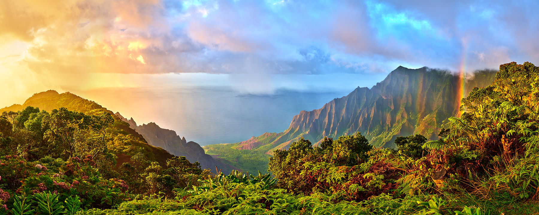 panoramic view of the Kalalau Valley on the island of Kauai with a rainbow and a dramatic sunset along the Na Pali Coast