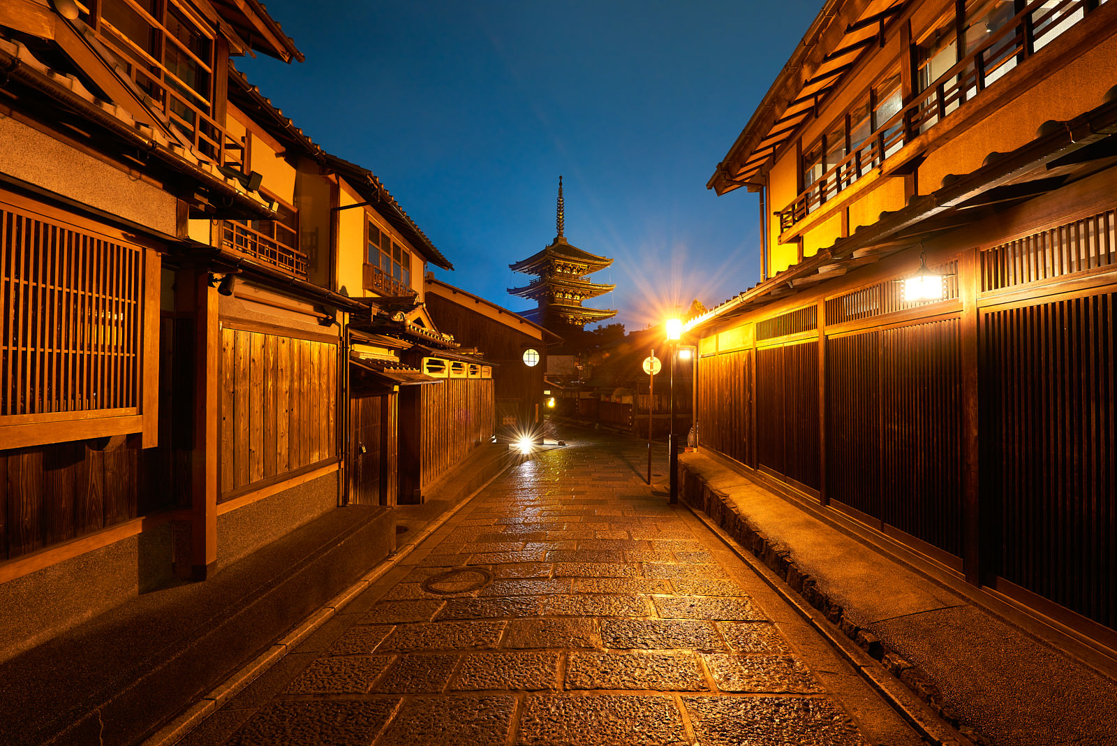 Street view in the well preserved Higashiyama district in Kyoto, Japan with a pagoda in the background at night