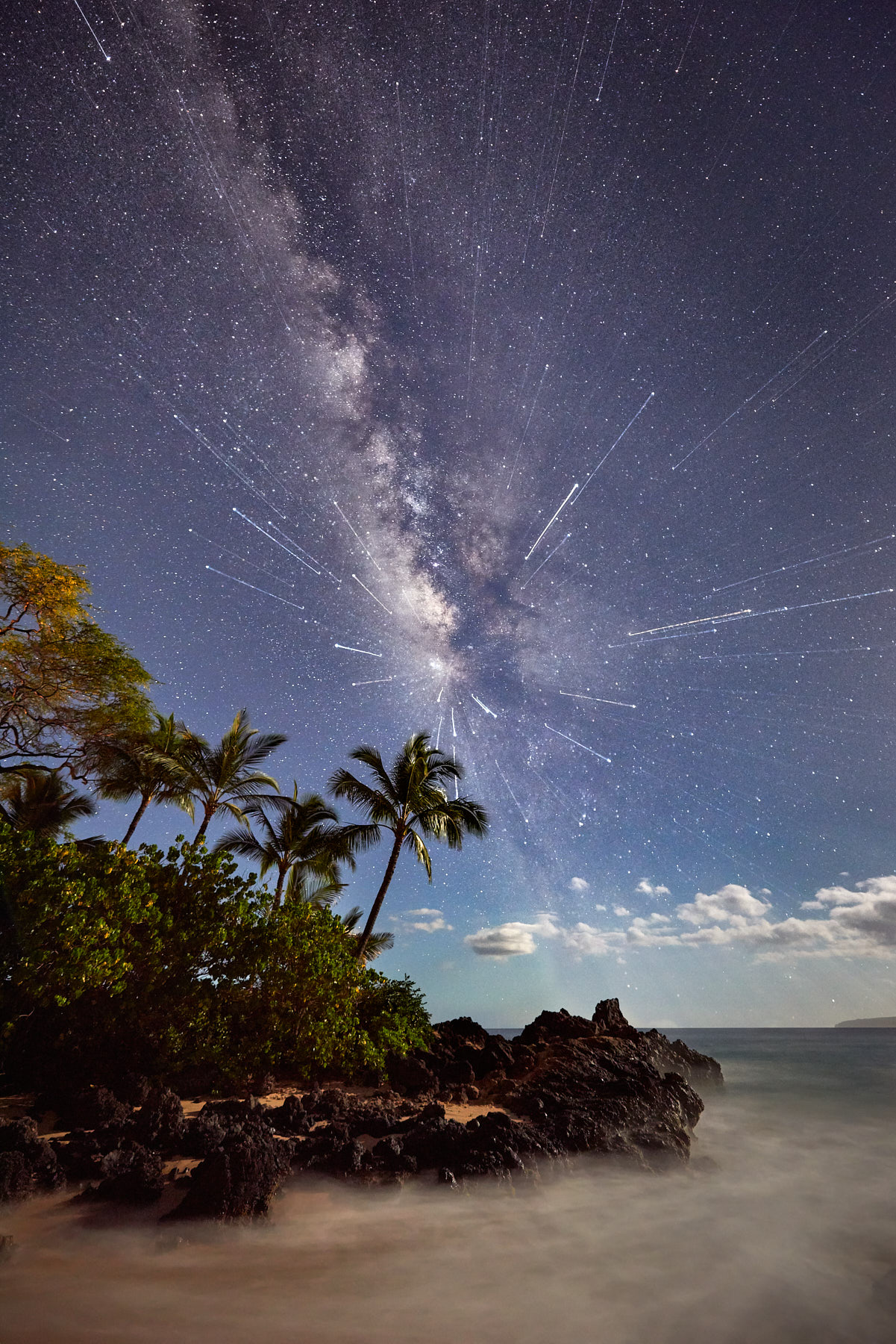 a mix of two long exposure photographs and one with a zoom lens gives a hyperspace effect to this milky way night scene at Secret Beach in Makena Maui