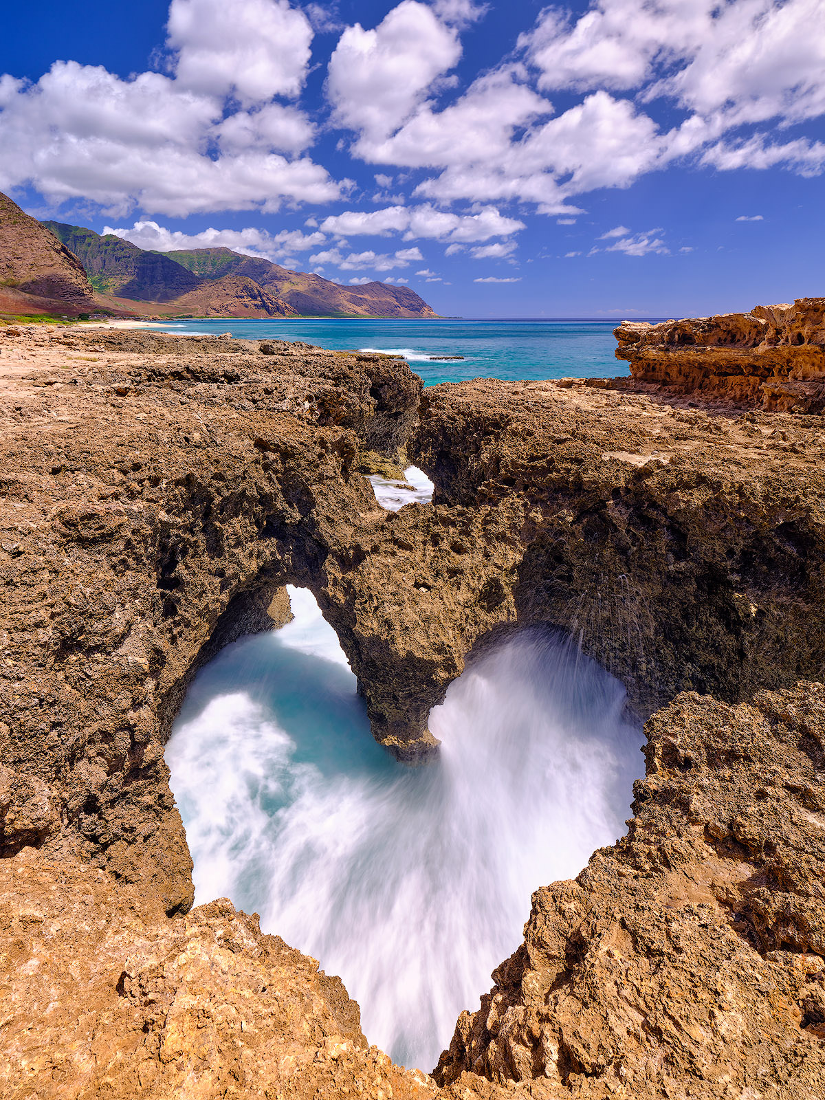 photograph of a heart shaped rock formation with incoming waves on the west side of the hawaiian island of Oahu. High resolution photography by Andrew Shoemaker