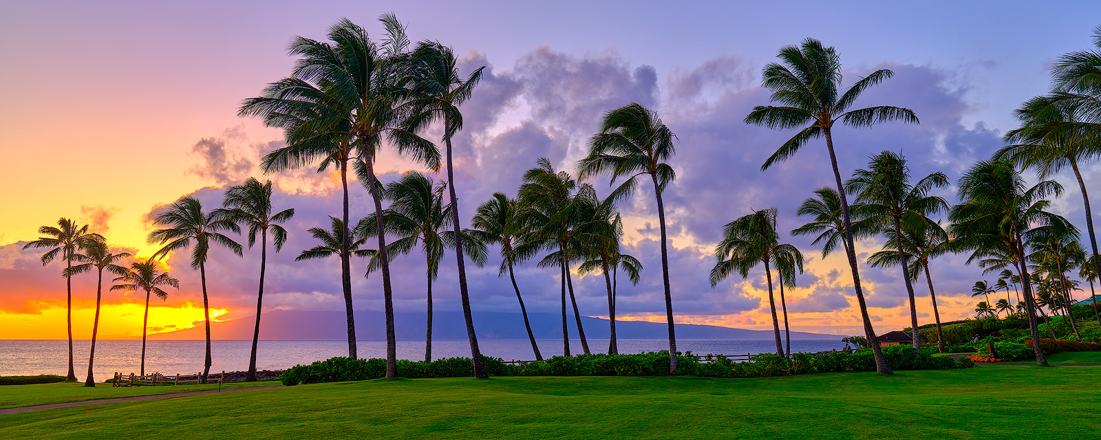 a panoramic scene at Kapalua Bay on the island of Maui at sunset with coconut palms and the Hawaiian island of Molokai in the background.