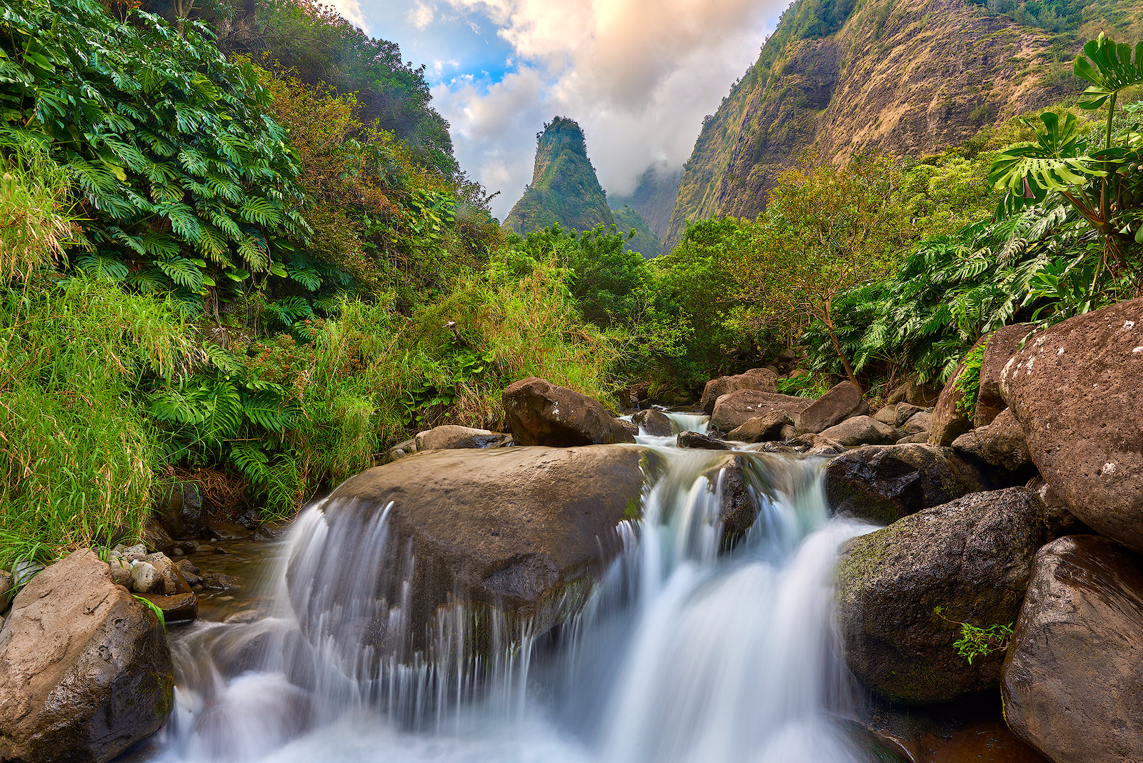 a waterfall flows over the rocks at Iao Valley State Park with the Iao Needle iconically in the background of the lush forest.  Hawaii Photography