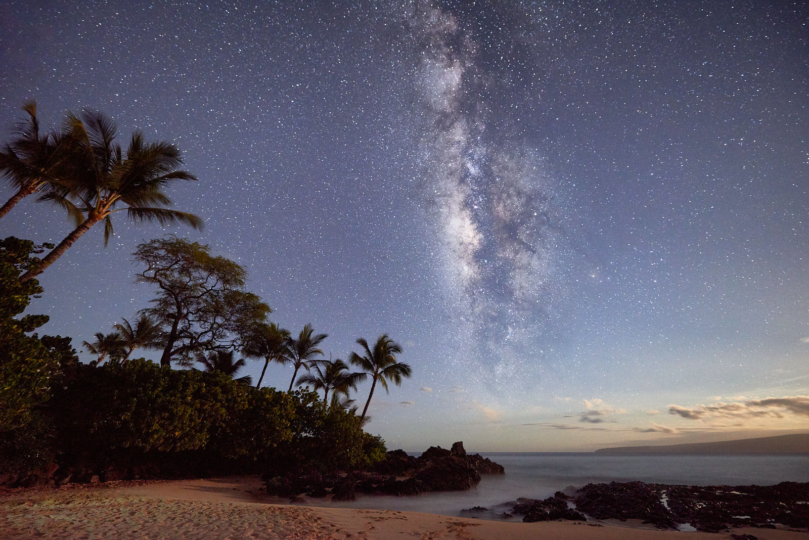 the core of the milky way galaxy is visible over the ocean with Makena Cove in the foreground illuminated by the moon
