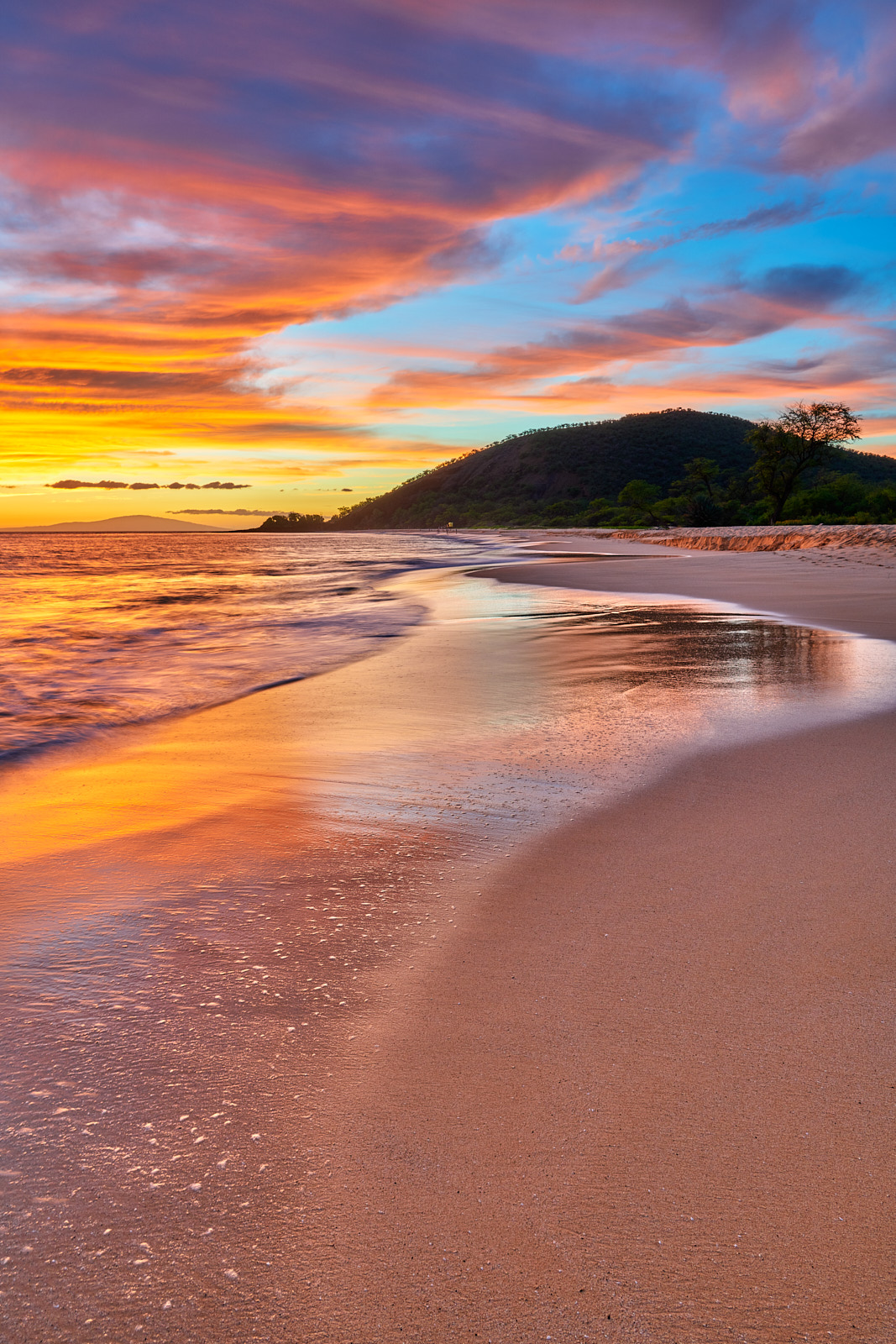 vertical photograph of sunset at Big Beach at Makena State Park in Maui, Hawaii.   The sunset clouds seems to mirror the incoming waves on the beach