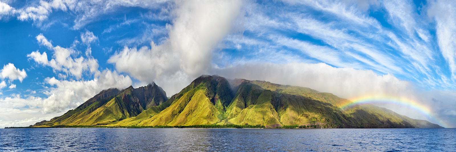 panorama of the island of Maui photographed from a boat off of Olowalu featuring a rainbow
