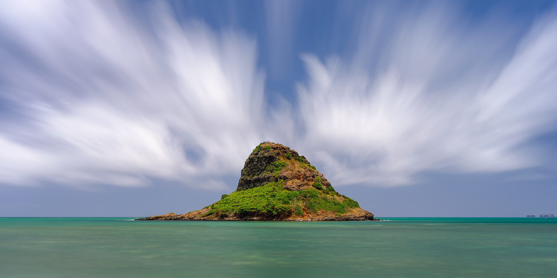 a long exposure of chinaman's hat on the hawaiian island of Oahu.  Also known as Mokoli'i Island, a beautiful scene captured by photographer Andrew Shoemaker