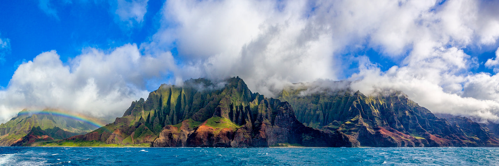 panoramic photo of the Na Pali coastline on the Hawaiian island of Kauai featuring a rainbow, dramatic clouds, and vibrant blue water