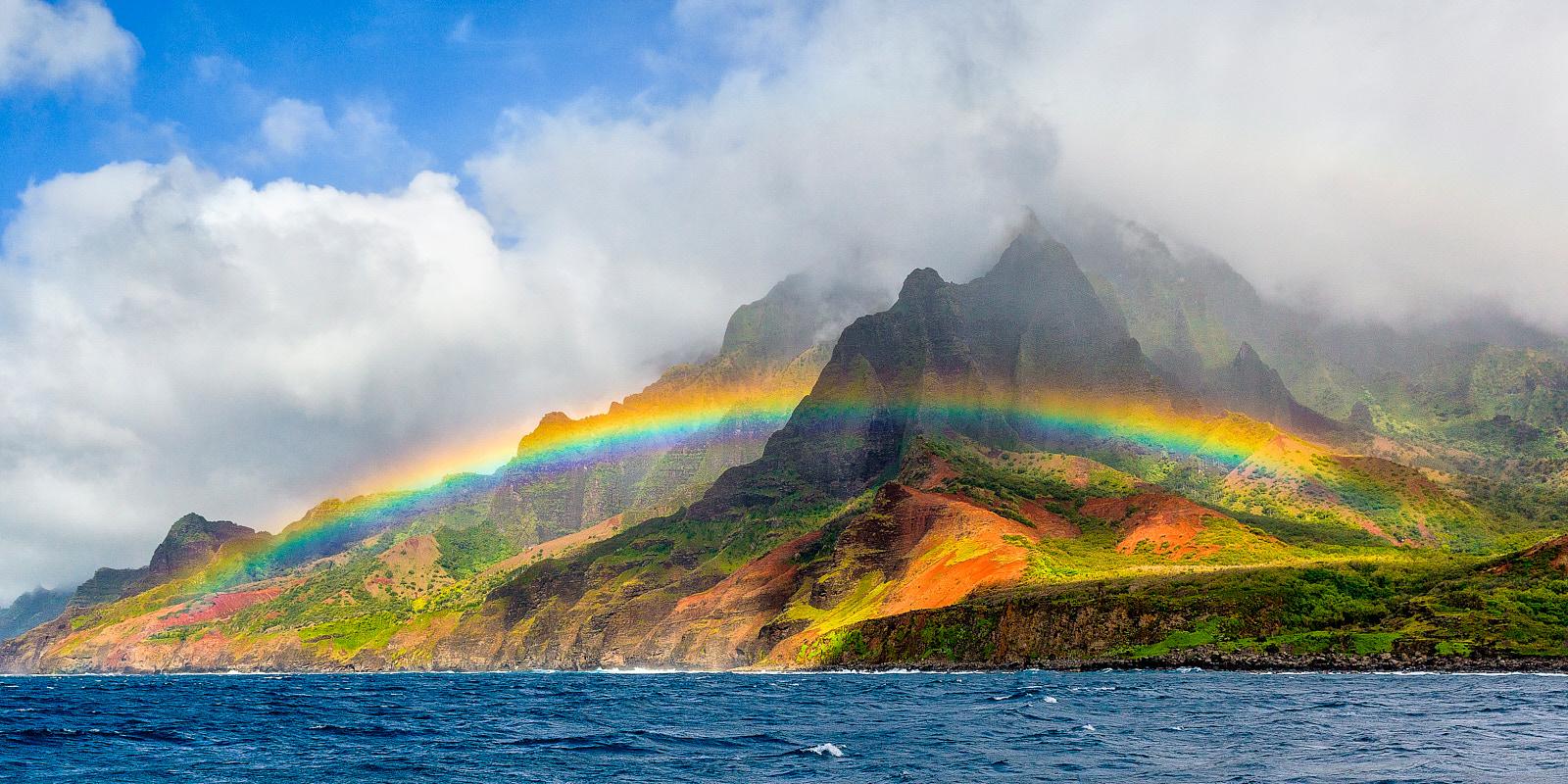 A panoramic view of a vibrant rainbow along the na pali coast on the Hawaiian island of Kauai