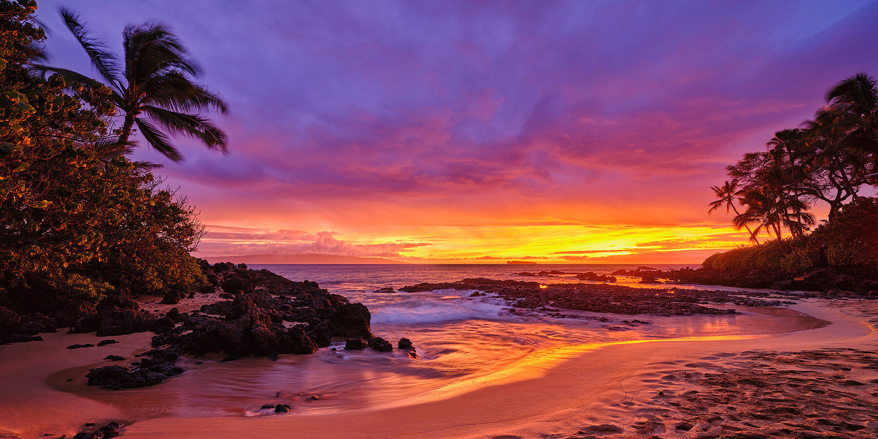 panorama of a very dramatic and vibrant colored sunset erupts at Secret Beach in Makena on the island of Maui