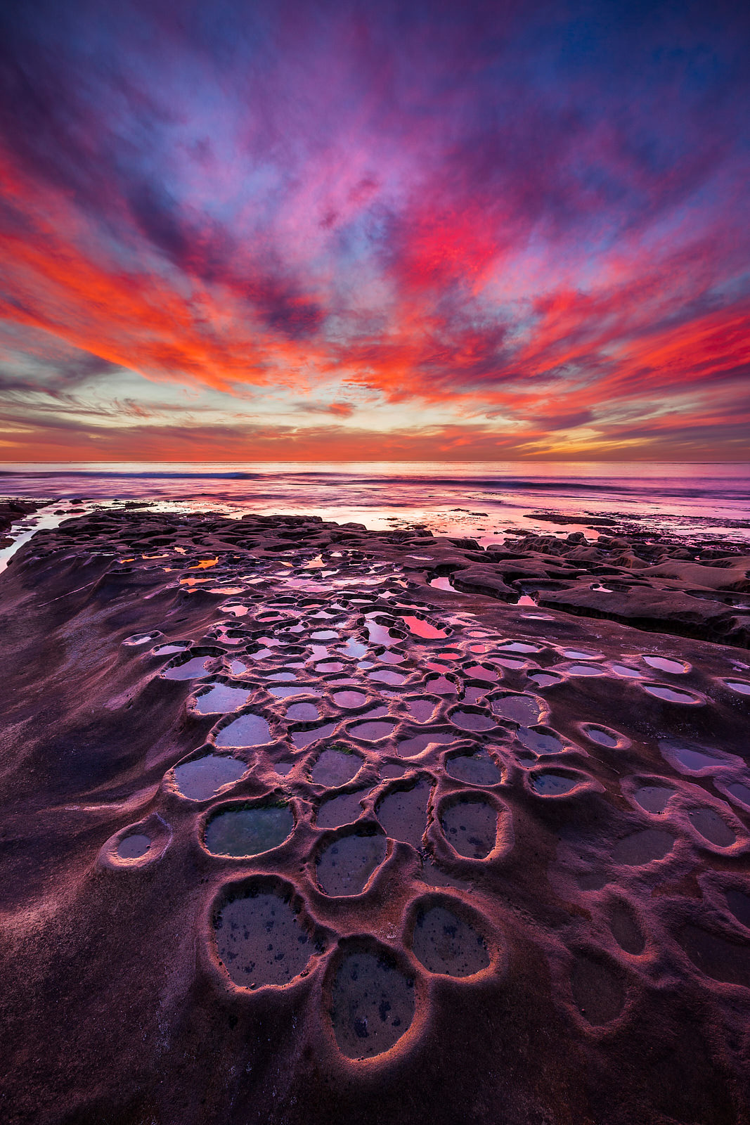 purple, red, and blue vibrant sunset over a very unique reef formation with the ocean along the coastline of La Jolla, California