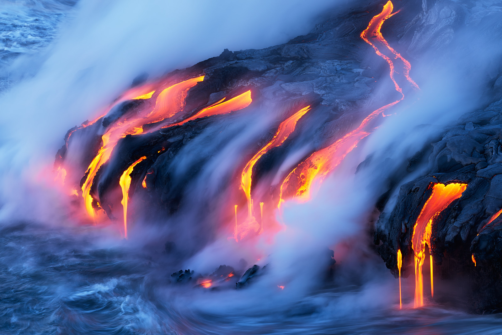 lava entering the ocean just before sunrise on the Big Island of Hawaii at Volcanoes National Park.