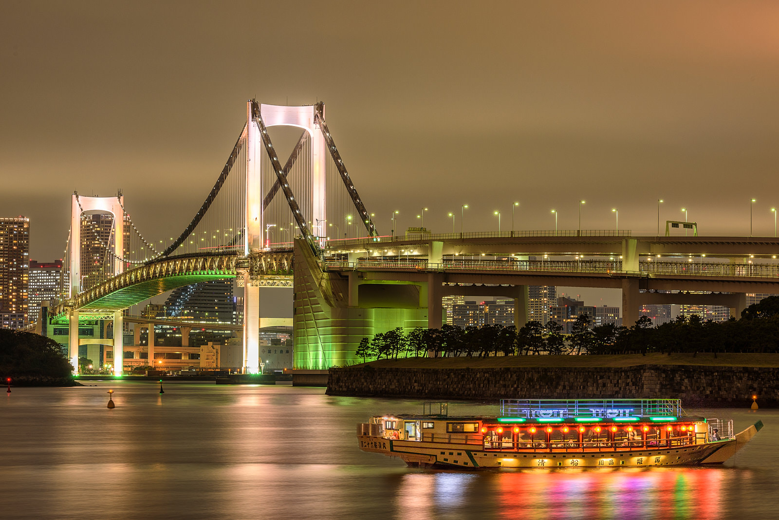 rainbow bridge in Tokyo, Japan illuminated at night with a colorful boat/taxi in the water