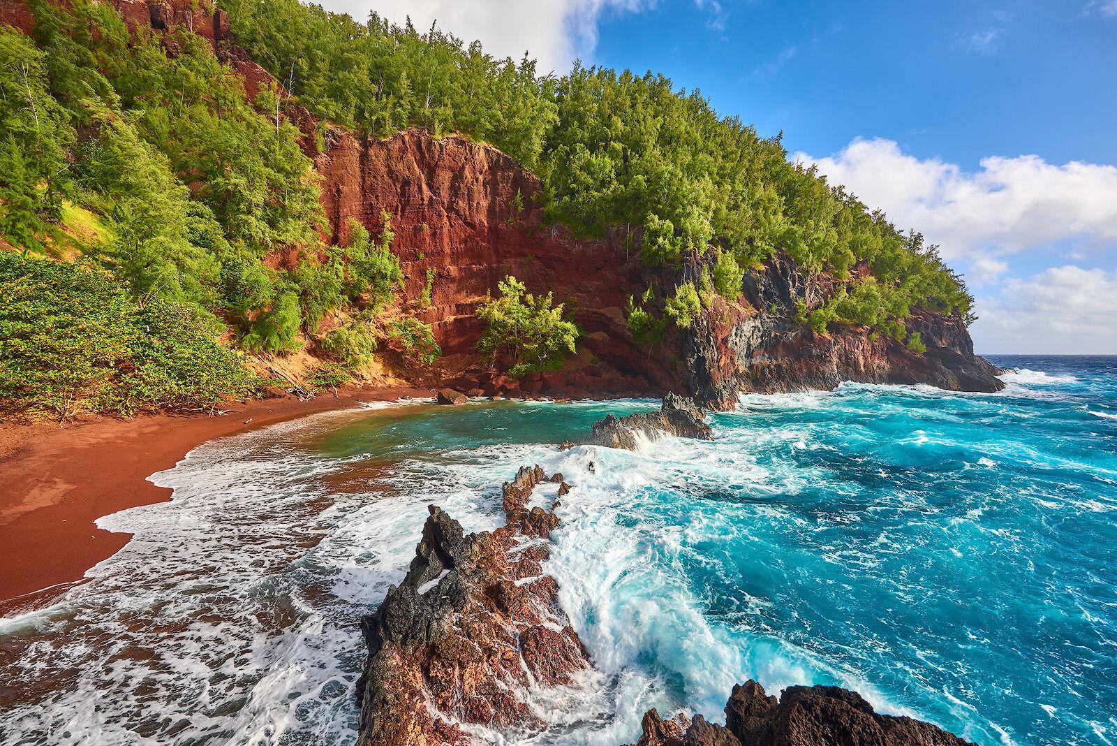 an amazing red sand beach with incoming aqua blue waves located in Hana, Hawaii on the island of Maui