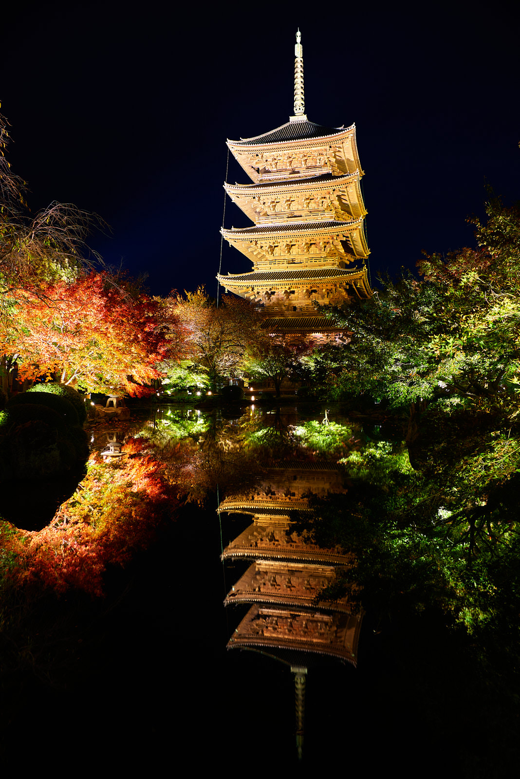 night image of an illuminated pagoda and fall colors reflecting into the water which appears like a mirror